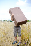 Little boy lifting up big old suitcase in wheat Stock Photo
