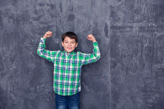 Little boy like superman. On the background of a concrete wall Stock Photo