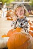 Little Boy lindo da los pulgares para arriba en el remiendo de la calabaza Imagenes de archivo