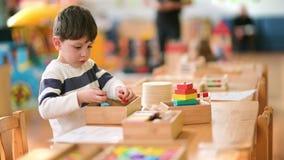Little Boy lindo que juega en la guardería con el juguete de la construcción almacen de metraje de vídeo