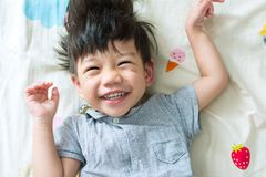 Little Boy lindo que sonríe en el sofá fotografía de archivo libre de regalías