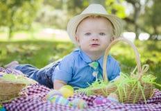 Little Boy lindo sonríe con los huevos de Pascua alrededor de él Foto de archivo
