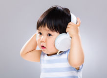 Little boy listen to the music and holding the headset Royalty Free Stock Images