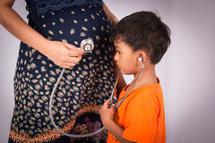 little boy listen to a stethoscope belly Royalty Free Stock Image