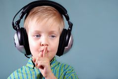 Little boy listening music on headphones. sign quieter royalty free stock images