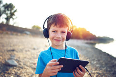Little boy listening music on tablet in outdoor sunset Stock Images