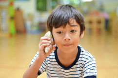 Little boy listening shell noise of sea Royalty Free Stock Photos