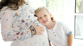 Pregnant woman with little son on window sill stock photography