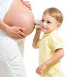 Little boy listening to her pregnant mother belly Royalty Free Stock Images