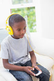 Little boy listening to music on the couch Stock Photo