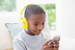 Little boy listening to music on the couch Stock Photography