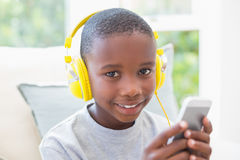 Little boy listening to music on the couch Stock Images