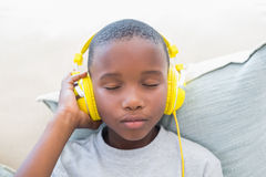 Little boy listening to music on the couch Stock Image