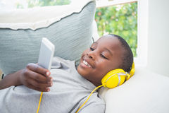 Little boy listening to music on the couch Royalty Free Stock Photo