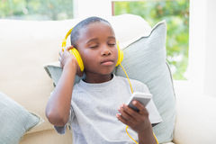 Little boy listening to music on the couch Royalty Free Stock Image