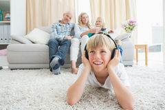 Little boy listening to music on the floor. At home in the living room Stock Photos