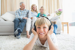 Little boy listening to music on the floor. At home in the living room Royalty Free Stock Photos