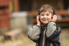 Little boy listening to music on headphones in the street Royalty Free Stock Photography