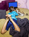A little boy with a little dog looking at a laptop. A little boy with a Terrier Yorkshire look at laptop lying in bed Royalty Free Stock Photography