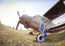Little boy and little girl pilot near the retro airplane Royalty Free Stock Images