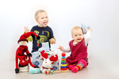 Little boy and little girl playing with Christmas gifts and toys isolated over white background. Stock Photography