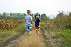 Little boy and little girl playing outside on field gravel road Stock Images