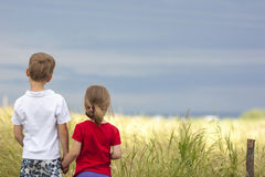 Little boy and little girl standing holding hands looking on hor Stock Photos