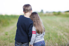 Little boy and little girl standing holding hands looking on hor Stock Photo