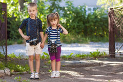 Little boy and a little girl wit two vintage cameras standing to Royalty Free Stock Images