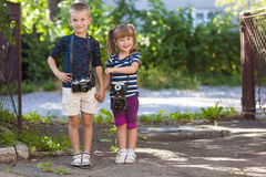 Little boy and a little girl wit two vintage cameras standing to Stock Photos