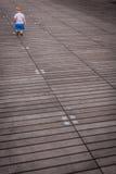 Little boy on a lonely walk. Little boy walking on a wooden planks in a harbour stock image