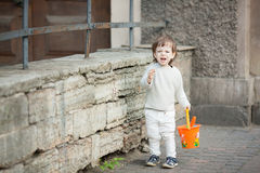 Little boy with long blond hair crying standing on the street. In his hand he is holding an orange bucket to play in the sandbox.  Stock Photos