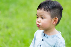 Little boy look at other side with funny face. Asian young little boy at outdoor royalty free stock photography
