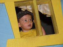 Little boy lookinf out window 48. Photo image of a little boy looking out of a playhouse window with a surprized look Royalty Free Stock Photography