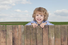 Little boy looking from above a fence, Royalty Free Stock Photo