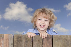 Little boy looking from above a fence, Royalty Free Stock Images