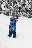 Little Boy Looking Back in a Snowy Forest stock photo