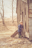 Little boy looking in barn Stock Photos
