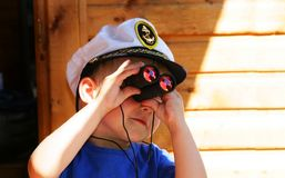 Little boy looking through the binocular stock images