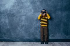 Little boy looking through binoculars on a dark blue background with a happy face standing stock images