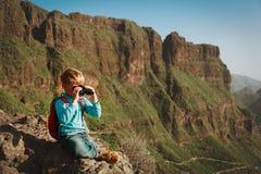 Little boy looking through binoculars travel in mountains. Little boy looking through binoculars hiking travel in mountains stock photo