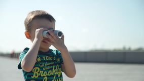Little Boy Looking Through Binoculars. While Playing on the River Embankment in Summer Day. Travel and Adventure concept stock video