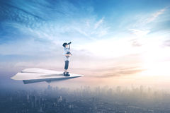 Little boy looking with binoculars. Picture of little boy standing on a paper aeroplane while flying above city and looking with binoculars Royalty Free Stock Photography