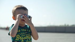 Little Boy with Binoculars in Summer Day. Little Boy Looking Through Binoculars While Playing on the River Embankment. Slow Motion. Happy Childhood concept stock video