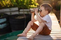 Little boy looking through binoculars on river bank Royalty Free Stock Images