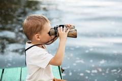 Little boy looking through binoculars on river bank Stock Image