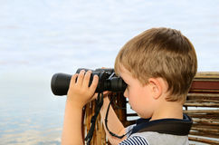 Little boy looking through binoculars at sea. side view Stock Images