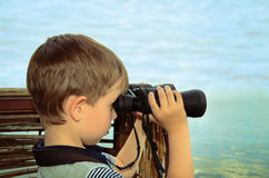 Little boy looking through binoculars at sea. side view, toning Stock Images