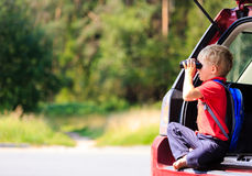 Little boy looking through binoculars travel by car Royalty Free Stock Photo