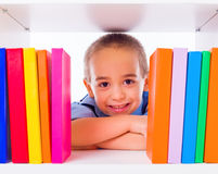 Little boy looking through book shelf Stock Image